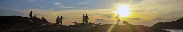 kajakkpadlere i solnedgang